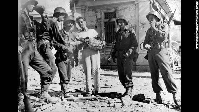 Persevere and you'll find many Sicilians transform from standoffish to almost overwhelmingly hospitable -- here a man offers wine to U.S. troops during World War II.