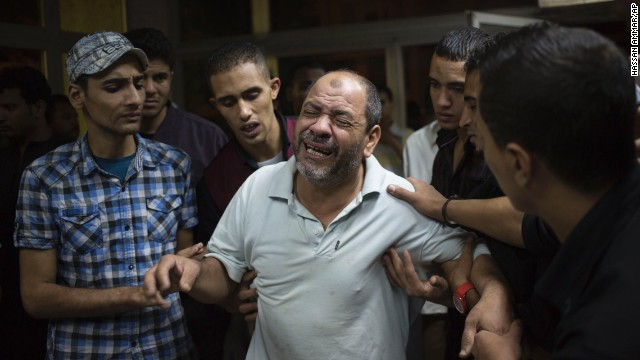 Bystanders try to comfort a man as he grieves for a relative slain during clashes October 6 in Cairo.