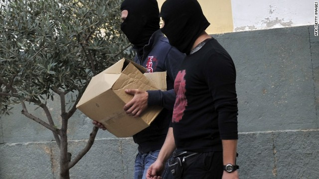 Anti-terror police bring a box containing the case file against an arrested extreme far-right Golden Dawn party member to an Athens court on October 2, 2013.