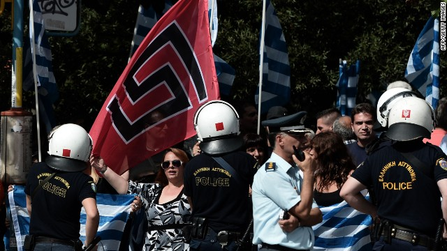Supporters of Golden Dawn wave the party's flag along with Greek flags during a protest outside a court in Athens on October 2, 2013.