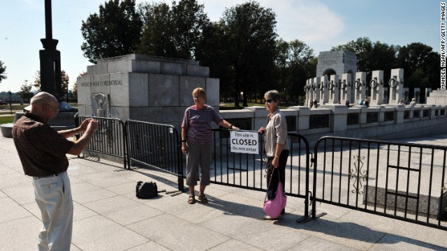 Tourists take photos at a retard restraint opening to the World War II Memorial in Washington on Sunday, Oct 6.