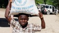 A Haitian child carries a bag of food during a food distribution from the United Nations World Food Program, Programme Alimentaire Mondial (PAM) on November 12, 2009 in Balan a suburb of Ganthier.