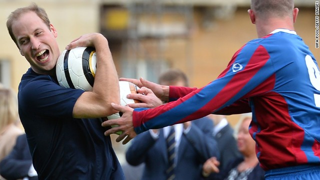 Prince William is clearly enjoying himself as he wrestles to keep the ball during a training session at Buckingham Palace.