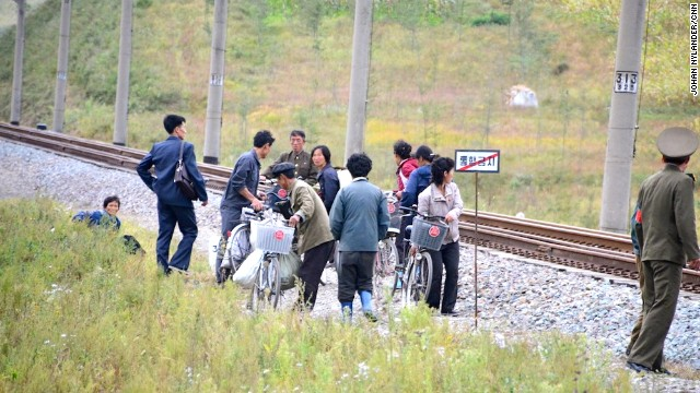 People standing by the train track, while a guard is monitoring the bike race.