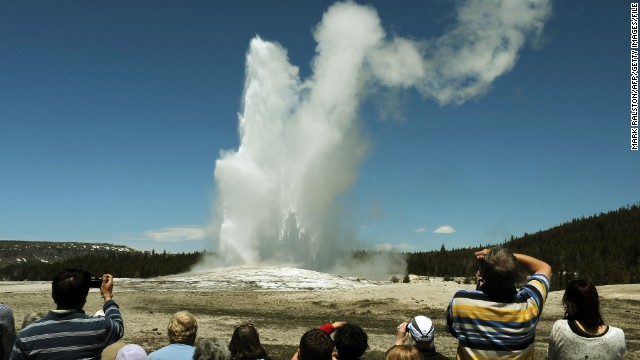 Tourists watch the Old Faithful geyser in the Yellowstone National Park in Wyoming in June 2011. One tourist told a Massachusetts newspaper that National Park Service guards treated members of her tour group brusquely and told them not to
