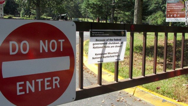 Metal gates closed with a chain block the entrance to Kennesaw Mountain National Battlefield Park, in Kennesaw, Georgia on Thursday, October 3. A sign posted on the gates announces the park's closure, citing the government shutdown.