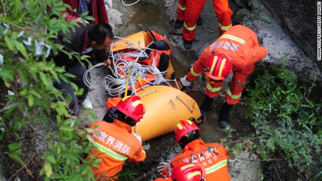 Rescuers carry the body of Kovats down a steep path in Tianmen Mountain National Forest Park on October 9.