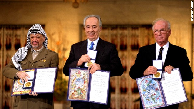Palestinian leader Yaser Arafat, left, Israeli Foreign Minister Shimon Peres, center, and Israeli Prime Minister Yitzak Rabin hold up their awards after winning the Nobel Peace Prize in 1994.