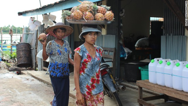 Women in Bogale take pineapples from boats on the nearby river to street markets to sell. Bogale is virtually surrounded by water and was one of the townships hardest hit by Cyclone Nargis in 2008.