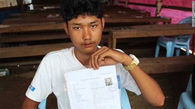 Zaw Min Paing poses with his army documentation. He was recruited at the age of 15 and spent more than four months in a training center before being released to his parents. He's now 19 and has given up hope of ever finishing school.