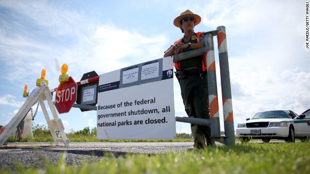A park ranger stands next to a road closed sign leading to the Everglades National Park in Miami on October 7.
