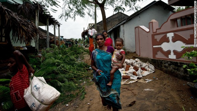 An Indian woman carries her child as they leave their home in Donkuru on October 12.