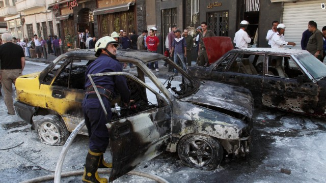 Firefighters extinguish a burning vehicle after two mortar rounds struck the Abu Roumaneh area in Damascus, Syria, on Saturday, October 12.