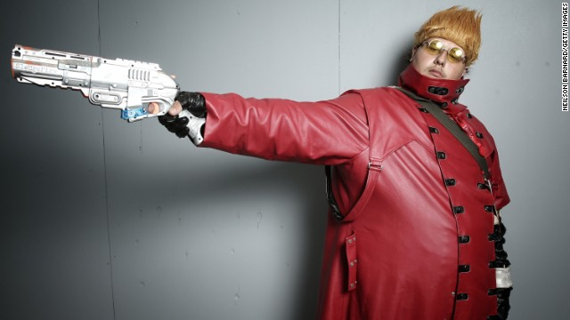 "This fan aims his gun as he poses as Vash the Stampede from the anime series ""Trigun."""