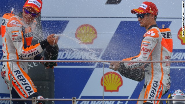 Dani Pedrosa sprays his Honda teammate and title leader Marc Marquez as he celebrates his Malaysian MotoGP win.