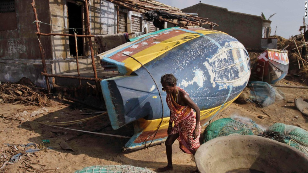 A woman walks near overturned boats in Pudumpeta, India, on Monday, October 14. Debris littered the streets and gaping holes were left in buildings after Tropical Cyclone Phailin pounded the eastern coast of India. Massive evacuation efforts helped limit the number of casualties.