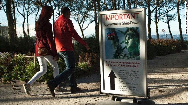A couple walks next to a sign October 12 informing them that the Statue of Liberty is closed. It reopened the next day on the state of New York's dime.