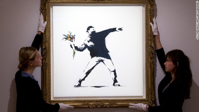 "Gallery assistants adjust Banksy's ""Love Is in the Air"" ahead of an auction in London on June 24. The piece was sold for $248,776."