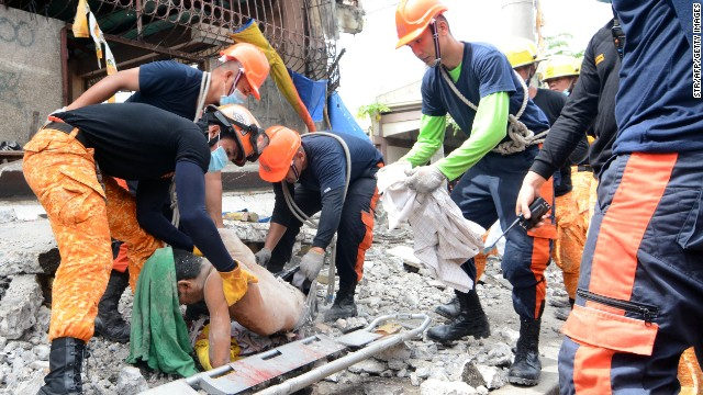 Rescuers pick up the body of a dead man in Cebu City after a 7.1 magnitude earthquake struck the region on October 15.