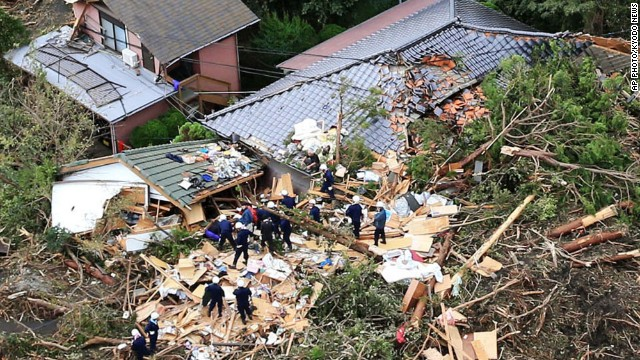 Rescue workers look for survivors as they stand on the rubble of a house buried by mudslides after a powerful typhoon hit Oshima island, about 120 kilometers (75 miles) south of Tokyo on Wednesday.