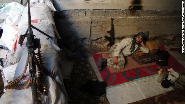 An opposition fighter rests on the front lines in the northeastern Syria city of Deir Ezzor on Tuesday, October 15.