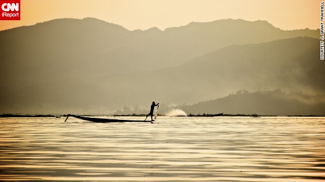 "A ""leg spinner"" paddles across Inle Lake. The unique style of paddling involves using one leg to power the boat while balancing on the canoe's edge with the other. This traditional method frees up the hands for fishing. See more photos of leg spinners in action on CNN iReport."