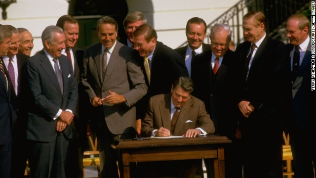 Reagan, surrounded by politicians, signs the Tax Reform Act of 1986. Democrats and Republicans sharply disagreed on how to amend the tax code, but both sides eventually compromised.