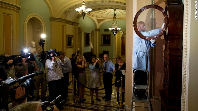 Museum specialist Richard Doerner winds the historic timepiece known as the Ohio Clock outside the Senate chamber on Thursday, October 17, the day after the partial government shutdown ended. The clock stopped during the 16-day shutdown when federal workers were furloughed. The federal government reopened after President Barack Obama signed a spending and debt ceiling agreement that Congress passed Wednesday night, October 16.
