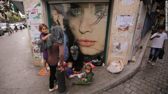 A Syrian refugee begs with her children Friday, October 18, on a street in Beirut, Lebanon.