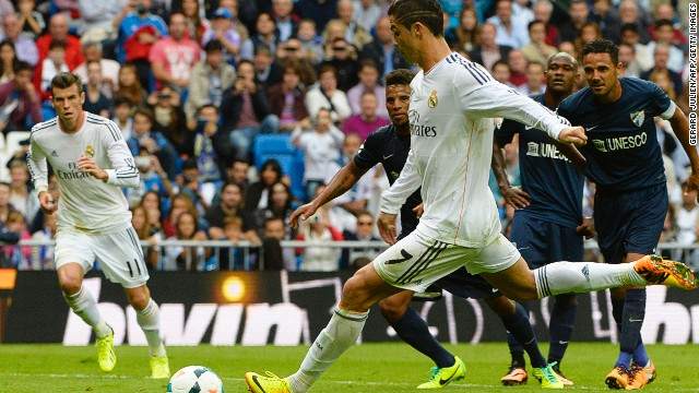 Gareth Bale (left) watches as Cristiano Ronaldo scores Real Madrid's second goal against Malaga from the penalty spot.