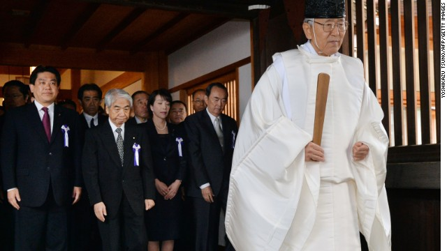 Japanese lawmakers follow a Shinto priest during a visit to the controversial Yasukuni shrine to honor the war dead at shrine's autumn festival in Tokyo on October 18, 2013.