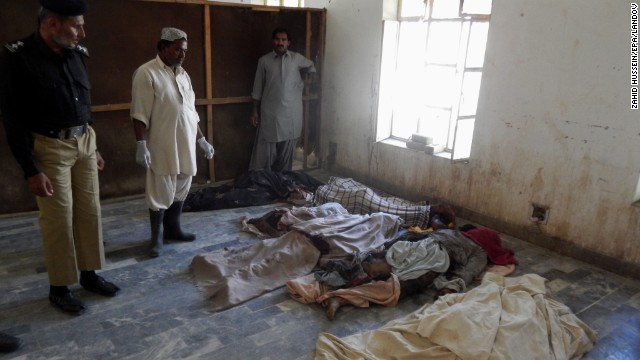 Security officials stand beside the bodies of victims from the blasts on October 21.