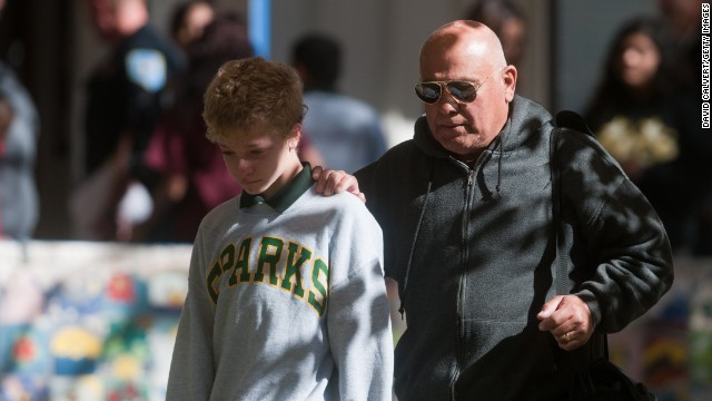A parent escorts his child from Agnes Risley Elementary School after a shooting Monday, October 21, at nearby Sparks Middle School in Sparks, Nevada. A student opened fire at the middle school, police said, killing a teacher and wounding two students.