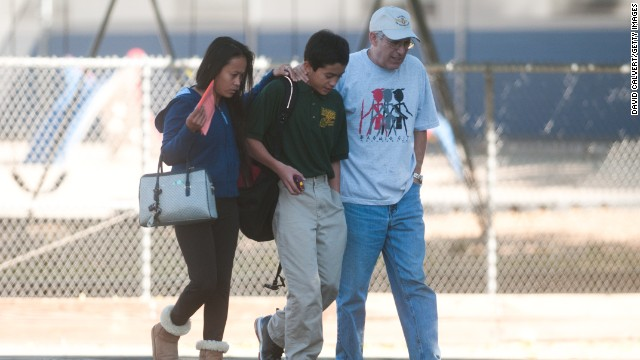 Parents escort a child from Agnes Risley Elementary School after the shooting.