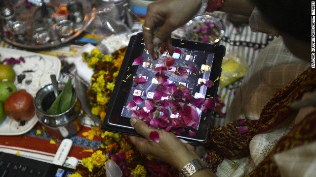 An Indian trader worships an iPad on Diwali, the Festival of Lights, in New Delhi on November 13, 2012. The worshipping of account books has long been an essential part of Diwali for the business community in India, and in a sign of the times some traders are now worshipping electronic gadgets as well.