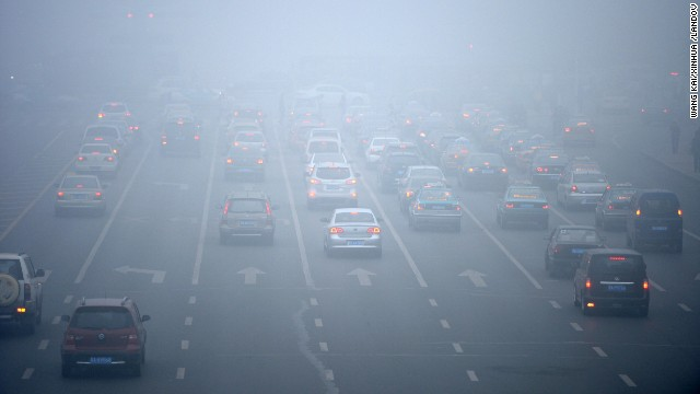 Drivers try to make their way through the smog in downtown Harbin on October 22.