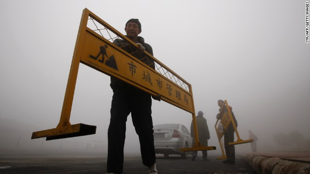 A workman carries a road barrier on a Harbin street on October 21.