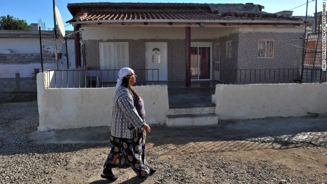 "A Roma woman walks next to the house where the family lived in Farsala. A spokesman for Smile of the Child, the charity that took Maria in, said the girl was found in ""bad living conditions, poor hygiene."""