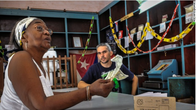 A shopkeeper talks to a customer in Santiago de Cuba, on July 10. Cuban government plans to end the dual-currency system.