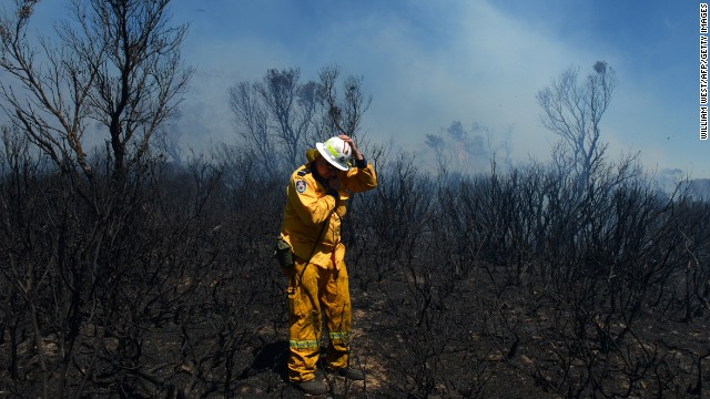 A volunteer firefighter holds onto his helmet as strong winds push through the Mount York fire area near the Blue Mountains on October 23.