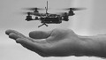 A quadrotor flying robot hovers above a man's hand
