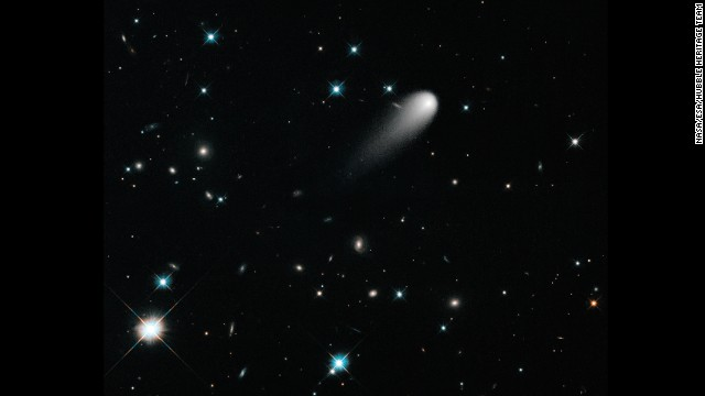 Comet ISON is seen against a backdrop of numerous galaxies and a handful of foreground stars.