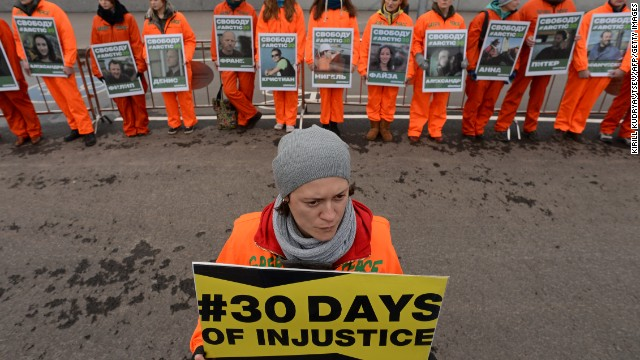 Greenpeace activists hold pictures of the detained 'Arctic 30' activists as they demonstrate in Moscow, on October 18, 2013.