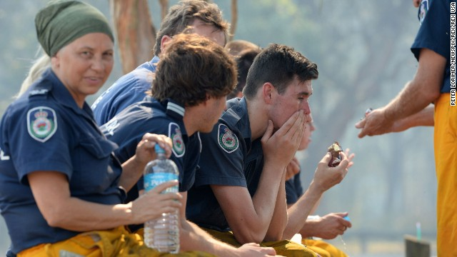 Firefighters rest as they wait for the fire front to jump a freeway in Newcastle, Australia, on October 23.