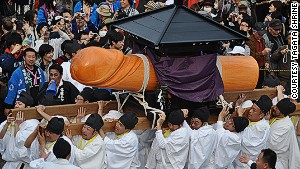 A team of men -- all aged 42 -- take turns carrying a 600-pound wooden phallus.