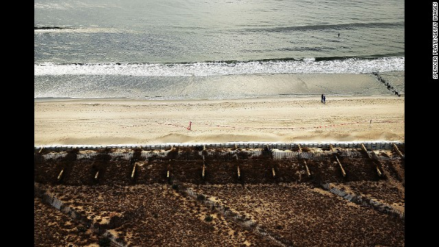 Two people walk along the beach where the boardwalk once stood on October 20 in Rockaway.