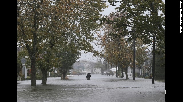 A person walks down South 9th Street in Lindenhurst, New York, as high tide, rain and winds flood area streets on October 29, 2012.