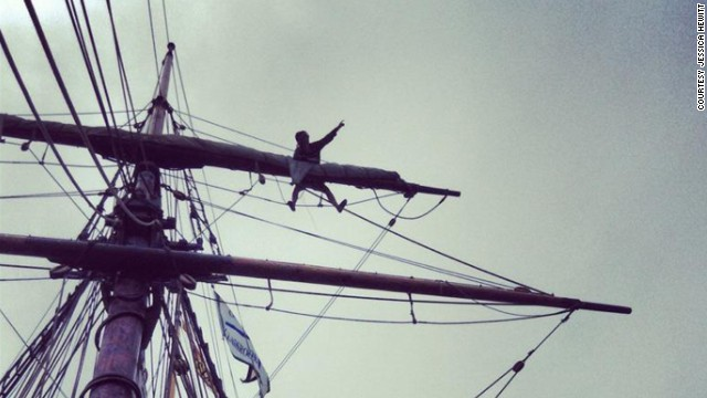 Hewitt climbs across a tall ship's yardarm, high above the deck.