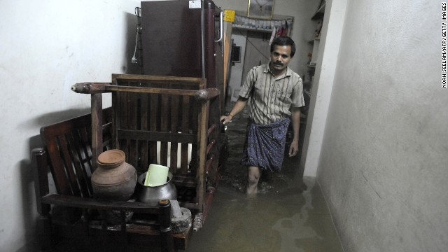 A resident walks through a flooded house following heavy rain in Saroornagar, a low lying area on the outskirts of Hyderabad on October 25.