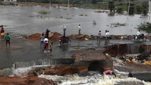 People wade through a flood-damaged road on the outskirts of Hyderabad on October 26.